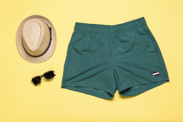 Chapéu masculino com óculos e calções de praia em um fundo amarelo. acessórios masculinos populares de verão.