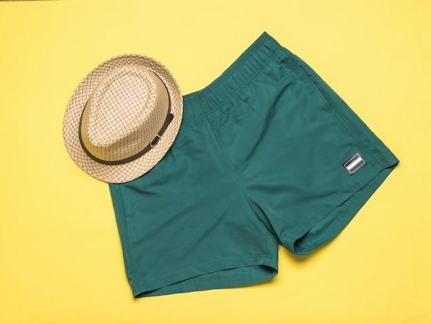 Chapéu masculino de verão e calção verde sobre fundo amarelo. acessórios masculinos populares de verão.