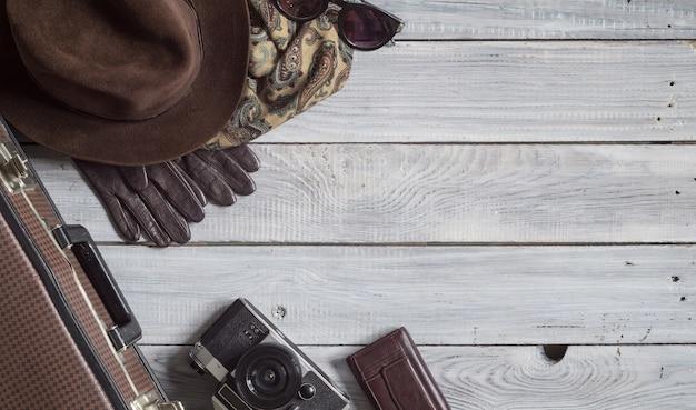 Chapéu masculino e acessórios retrô para viagens em uma superfície de madeira branca