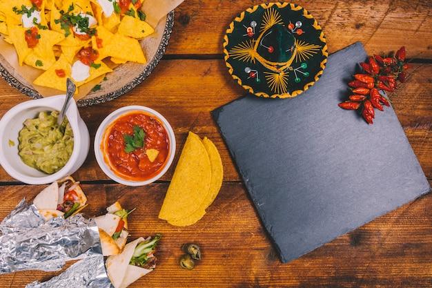 Chapéu mexicano; tacos embrulhados; nachos saborosos; molho de salsa; guacamole; ardósia preta e pimentões vermelhos na mesa