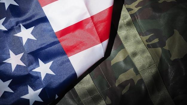 Chapéu militar ou bolsa com a bandeira americana. chapéu de soldado ou capacete com a bandeira nacional americana em fundo preto. representa o conceito militar por objeto de camuflagem e a bandeira da nação dos eua.