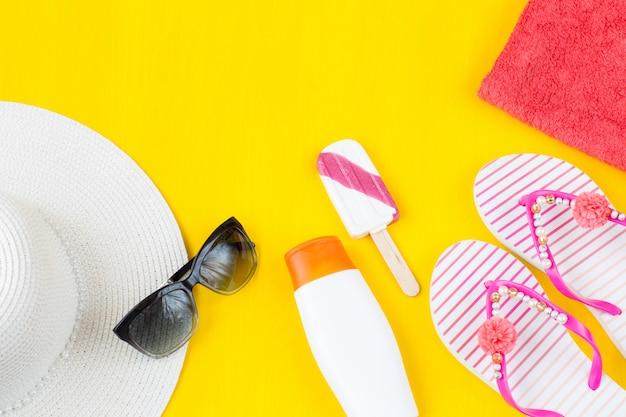 Chapéu, óculos de sol, sorvete, creme de proteção solar, toalhas e chinelos