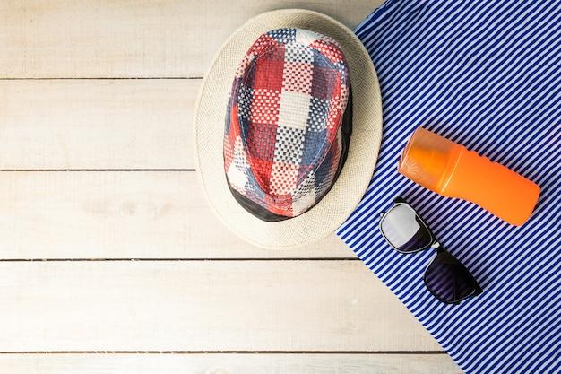 Chapéu, óculos e spray de proteção solar em toalha listrada, mesa de madeira branca