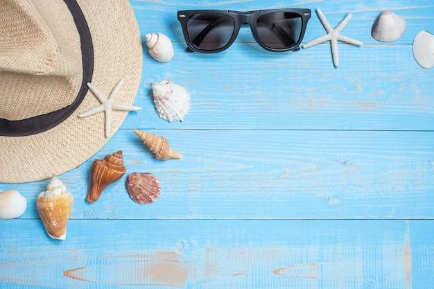 Chapéu, óculos escuros e concha em azul