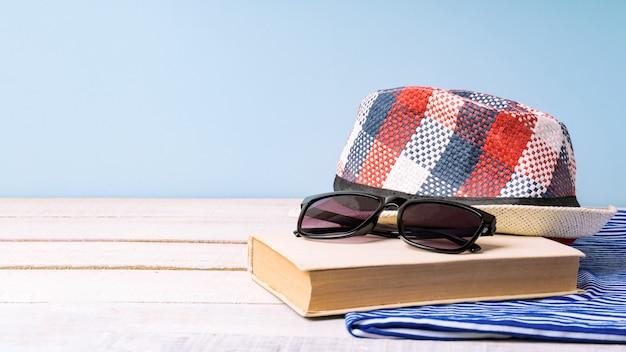 Chapéu, óculos escuros e um livro sobre uma toalha listrada, mesa de madeira branca