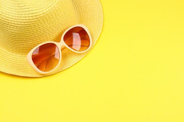 Chapéu, óculos escuros sobre um fundo amarelo pastel.
