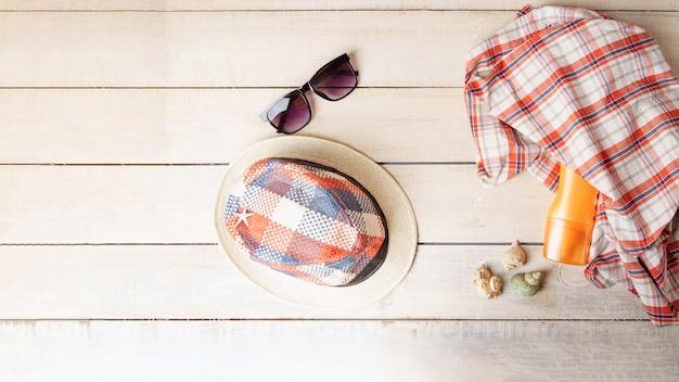 Chapéu, óculos escuros, spray de bronzeamento, toalha e conchas em uma mesa de madeira branca.