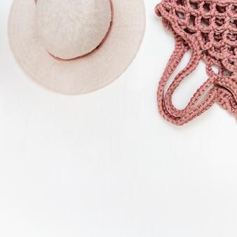 Chapéu para mulher e bolsa elegante na mesa de luz. conceito de férias. lay plana.