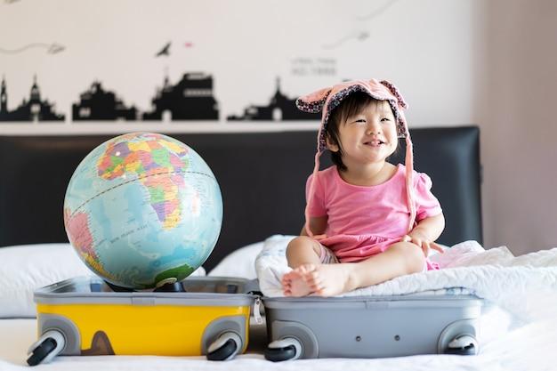 Chapéu pequeno bonito asiático do bebê que senta-se na mala de viagem com o sorriso que sente engraçado e que ri na cama no quarto com o globo do mundo posto no outro lado do saco da mala de viagem.