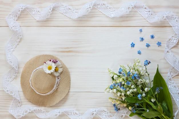 Chapéu pequeno, lírios do vale e rendas em um fundo branco de madeira.