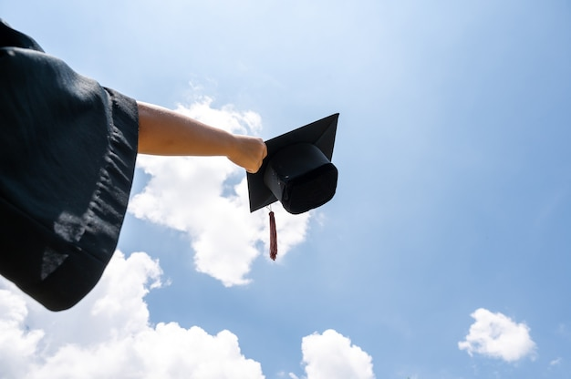 Chapéu preto dos graduados flutuando no céu.