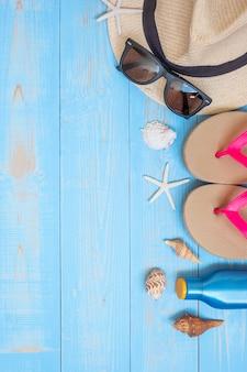 Chapéu, protetor solar, óculos de sol, chinelos e shell em azul