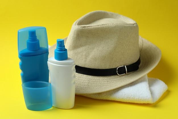 Chapéu, protetores solares e toalha em fundo amarelo isolado