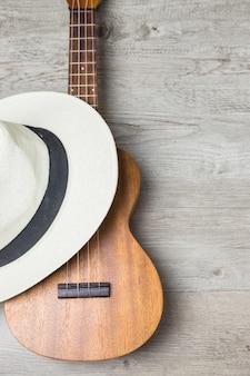 Chapéu sobre a guitarra de madeira contra o pano de fundo de prancha de madeira