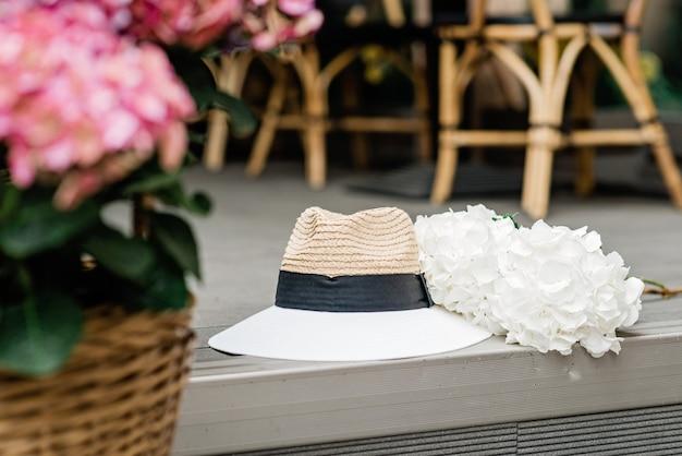 Chapéu solitário e flores de hortênsias brancas e rosa. fundo romântico da primavera e do verão. foco seletivo suave.