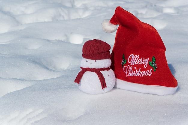 Chapéu vermelho de natal e um lindo brinquedo de boneco de neve no conceito de celebração do feriado de neve branca