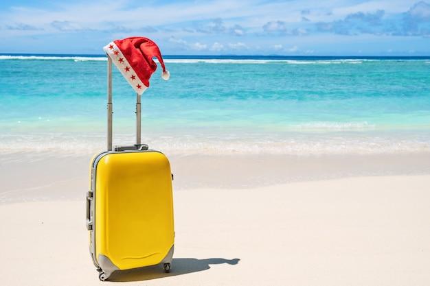 Chapéu vermelho de papai noel na alça de bagagem de viagem amarela com praia tropical