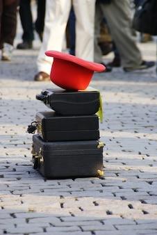 Chapéu vermelho nas malas de viagem velhas colocadas por um executor da rua na rua para executar uma mostra.