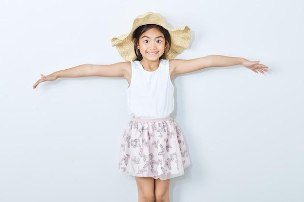 Chapéu vestindo da menina magro asiática no fundo branco.