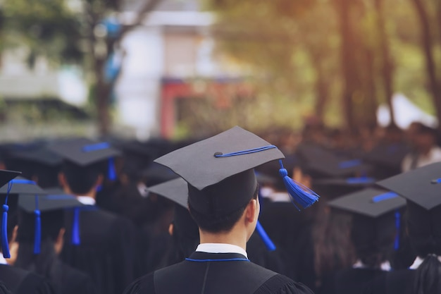 Chapéus de formatura na parte traseira durante os graduados de sucesso de formatura da universidade, parabéns da educação do conceito. cerimônia de graduação, parabenizou os formados na universidade durante o início