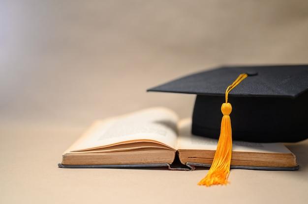 Chapéus de formatura preto colocados em livros abertos
