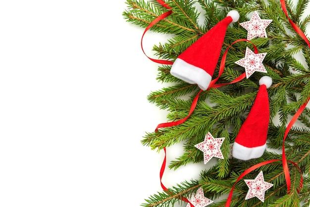 Chapéus de natal com galhos de pinheiro e estrelas em um fundo branco.