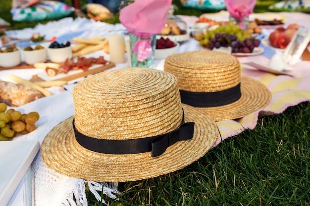 Chapéus de palha colocar em um cobertor de piquenique branco no gramado verde brilhante dia de verão