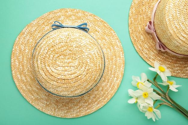 Chapéus de palha com flores da primavera na superfície da hortelã