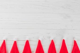 Chapéus de Papai Noel na mesa de madeira