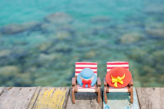 Chapéus diminutos na cadeira de praia com fundo do mar.
