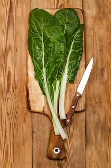 Chard em uma placa de cozinha de madeira em uma vista superior