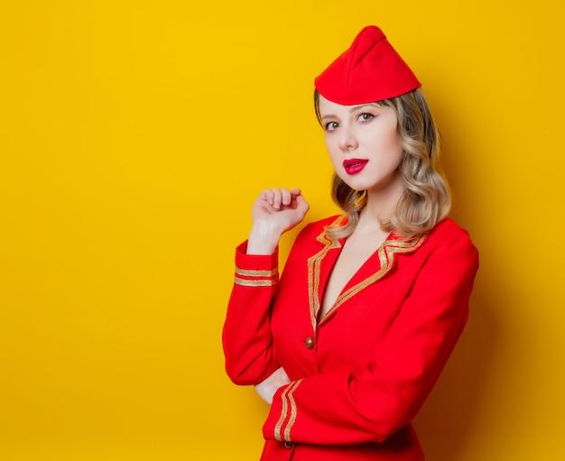 Charmosa aeromoça vintage vestindo uniforme vermelho