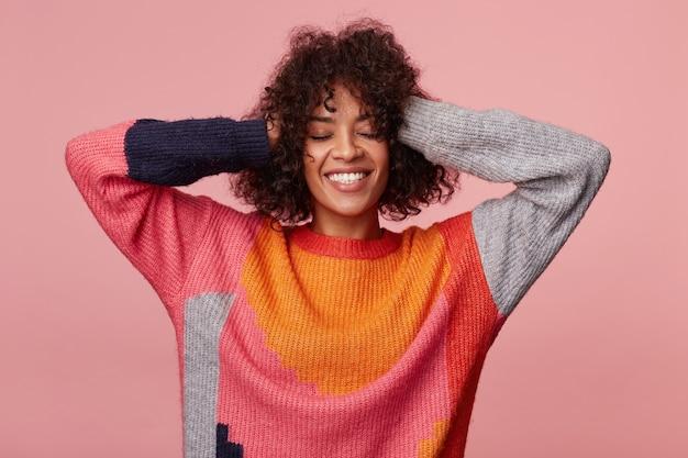 Charmosa garota afro-americana com penteado afro brincalhão leva as mãos à cabeça, se espreguiça, sorri relaxado, goza de olhos fechados, vestindo manga comprida colorida, isolado