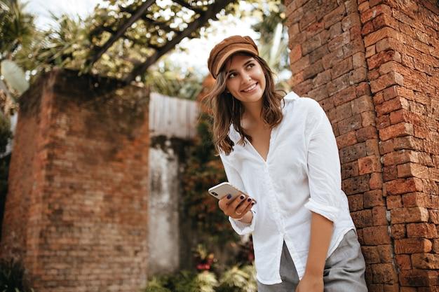 Charmosa garota de cabelo curto encostado na parede de um antigo prédio de tijolos, sorrindo e segurando o telefone. instantâneo de mulher de calça cinza e blusa branca.