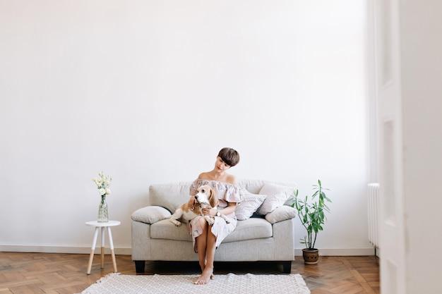 Charmosa garota descalça sentada no sofá cinza entre a mesinha e a planta verde, olhando para o cachorro beagle de joelhos