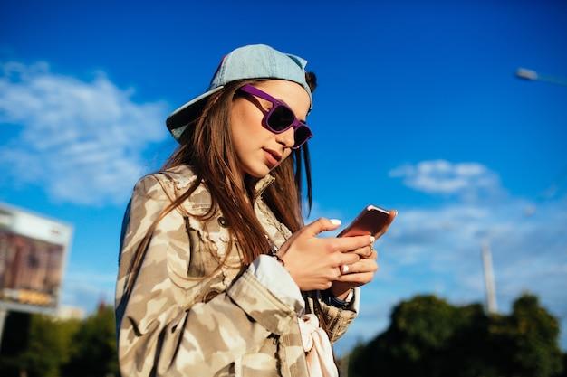 Charmosa jovem em óculos de sol, usando um telefone celular, navegando sites