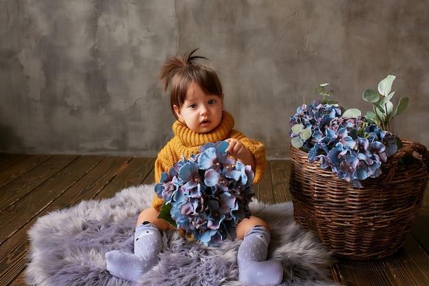 Charmoso bebê-menina em camisola laranja explora hortênsias azuis sentado no cobertor quente