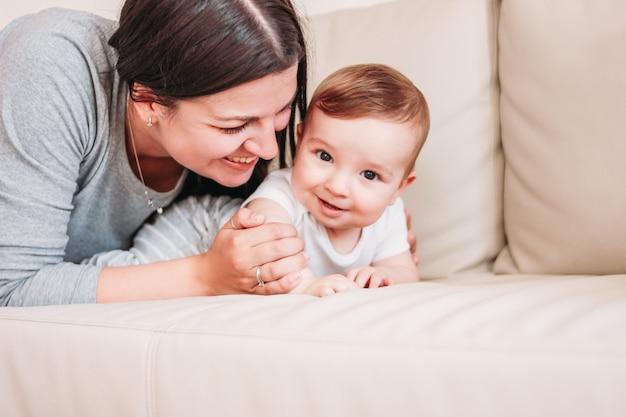 Charmoso bebezinho 6 meses com a mãe feliz no sofá em casa