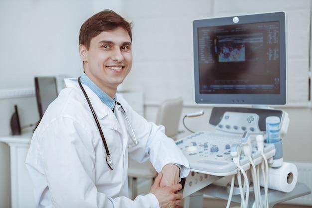 Charmoso jovem médico masculino sorrindo para a câmera, sentado em seu escritório perto da máquina de ultra-som