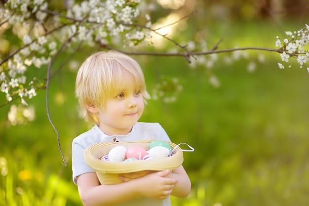 Charmoso rapaz caçando ovo de páscoa no parque primavera no dia de páscoa