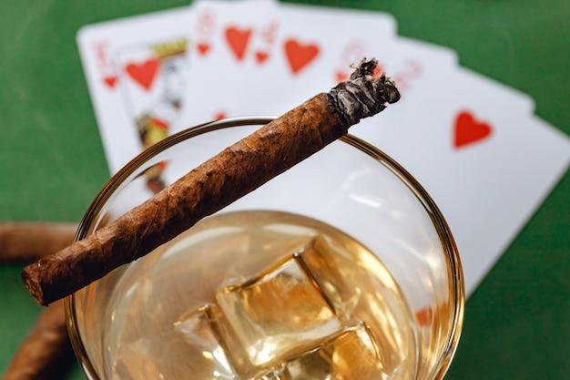 Charuto e cartas de jogar na mesa do cassino