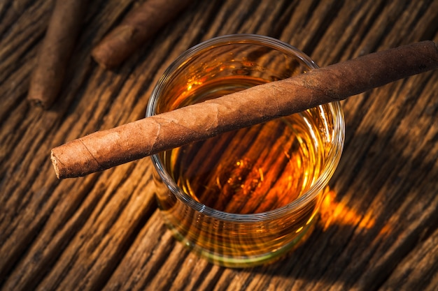 Charuto em vidro de uísque na velha mesa de madeira
