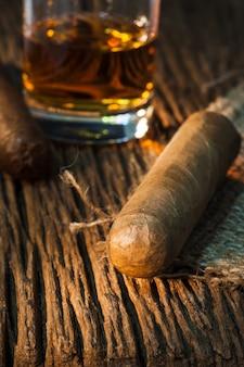 Charuto na velha mesa de madeira com o melhor whisky