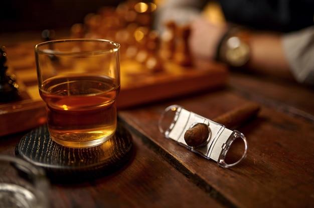 Charuto no cinzeiro e bebida alcoólica em vidro, isqueiro e guilhotina na mesa de madeira, vista superior. cultura de fumar tabaco, sabor específico. conceito de maus hábitos, ferramentas para fumantes