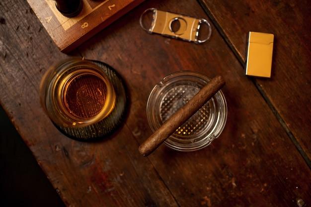 Charuto no cinzeiro e bebida alcoólica no vidro, isqueiro e guilhotina na mesa de madeira, vista de cima, ninguém