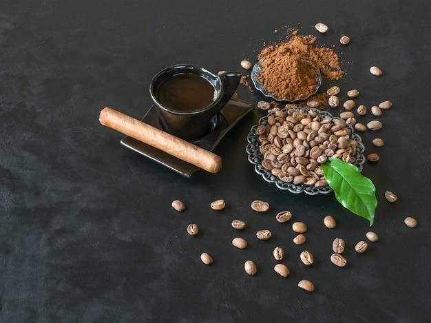 Charuto, xícara de café, grãos de café com pó moído em fundo preto.