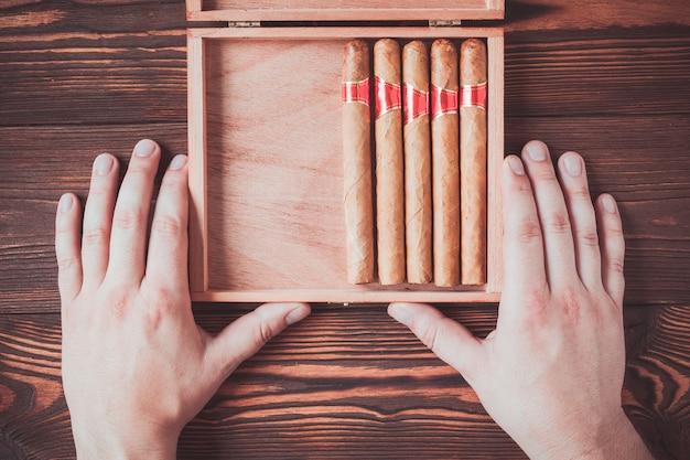 Charutos cubanos em uma caixa nas mãos masculinas em um fundo de madeira