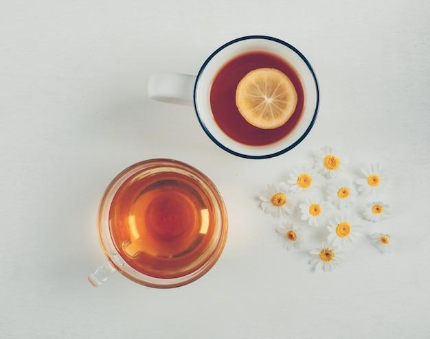 Chás e flores em xícaras. vista do topo.