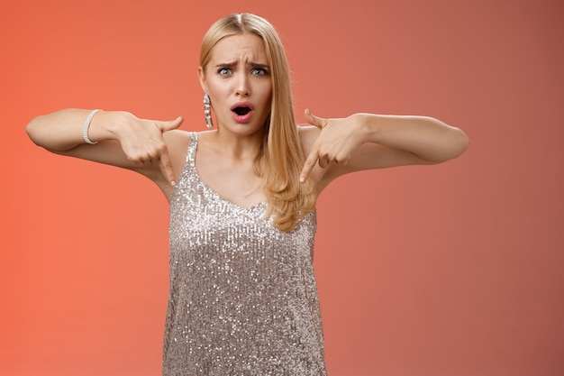 Chateada decepcionada enganada namorada loira elegante em vestido prateado franzindo a testa fazendo careta incomodada em apontar para baixo descontente não gostando de sapatos comprados na loja online não combinando com roupa, ficando infeliz