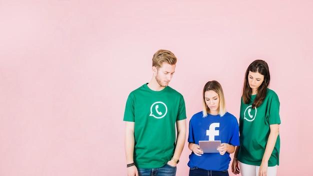 Chateado, amigos, olhar, tablete digital, ligado, fundo cor-de-rosa